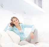 Una mujer morena joven que se relaja en una cama blanca imagen de archivo libre de regalías