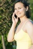 Una mujer morena que habla en el teléfono y que sonríe, en el verano en la calle Fotos de archivo