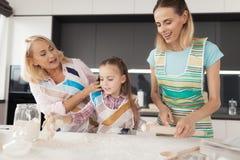 Una mujer, una muchacha y una mujer de mediana edad cocinan una torta hecha en casa La muchacha amasa la pasta Imágenes de archivo libres de regalías