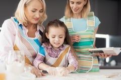 Una mujer, una muchacha y una mujer de mediana edad cocinan una torta hecha en casa La ayuda de la abuela y de la mujer la muchac Imagenes de archivo