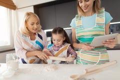 Una mujer, una muchacha y una mujer de mediana edad cocinan una torta hecha en casa La muchacha desarrolla la pasta Una mujer est Imágenes de archivo libres de regalías