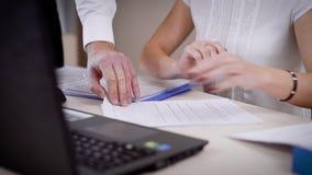 Una mujer muestra los cambios en los documentos jurídicos para su jefe, los hombres que las manos del ` s vuelcan las hojas de pa almacen de metraje de vídeo