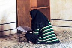 Una mujer musulmán con un pañuelo negro fotos de archivo
