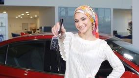Una mujer musulmán joven con llaves de un nuevo coche almacen de metraje de vídeo