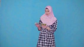 Una mujer musulmán joven considera un paquete de dinero satisfecho, mira la cámara almacen de metraje de vídeo