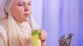 Una mujer musulmán joven en una bufanda ligera bebe un smoothie y sonrisas de la fruta almacen de metraje de vídeo