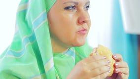 Una mujer musulmán joven en una bufanda verde clara en un café come una hamburguesa almacen de metraje de vídeo