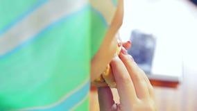 Una mujer musulmán joven en una bufanda verde clara en un café come una hamburguesa metrajes