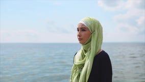 Una mujer musulmán joven en un velo viene con una mirada pensativa a lo largo del mar almacen de metraje de vídeo