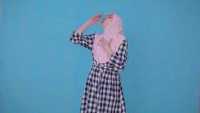 Una mujer musulmán joven que tiene un ataque de asma, utiliza el espray metrajes