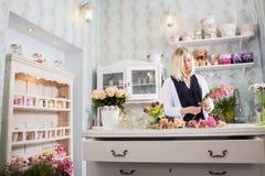 Una mujer muy dedicada a ella trabajo en la floristería Fotografía de archivo