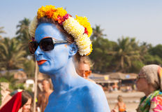 Una mujer no identificada con la piel azul en una guirnalda de la flor en el festival de monstruos, playa de Arambol, Goa, la Indi Imágenes de archivo libres de regalías