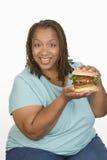 Una mujer obesa que sostiene la hamburguesa Imágenes de archivo libres de regalías
