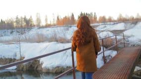 Una mujer pelirroja joven cruza un pequeño río a lo largo del puente en primavera temprana en la salida del sol almacen de video