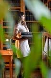 Una mujer pensativa con los libros a través de las hojas verdes Foto de archivo