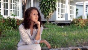 Una mujer pensativa hermosa joven se está sentando en el pórtico de su casa de campo almacen de video