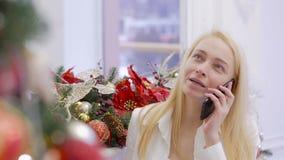 Una mujer pide una Navidad en su teléfono móvil para desear a un amado una Feliz Navidad cuando ella se está colocando delante de metrajes