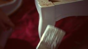 Una mujer pinta una silla antigua vieja con una nueva capa de la pintura blanca - grado del color del indie metrajes