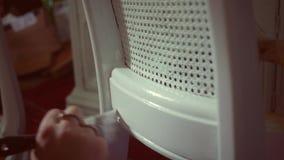 Una mujer pinta una silla antigua vieja con una nueva capa de la pintura blanca - PDA - grado del color del indie metrajes