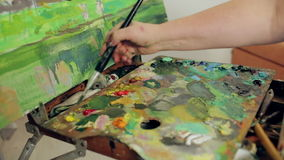 Una mujer pinta un paisaje con las pinturas de aceite con una paleta y un cepillo tiro del resbalador almacen de metraje de vídeo
