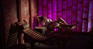 Una mujer pone en un ocioso de madera en una sauna de la sal en un hotel costoso Pared rosada Sauna terapéutica, terapia, medicin metrajes