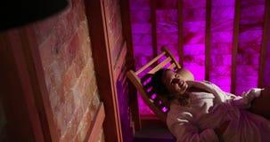 Una mujer pone en un ocioso de madera en una sauna de la sal en un hotel costoso Pared rosada Sauna terapéutica, terapia, medicin almacen de video