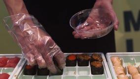 Una mujer pone los rollos de sushi en la placa metrajes