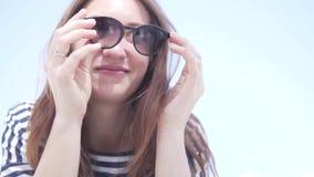 Una mujer pone sus gafas de sol de la cara