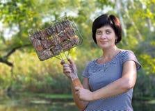 Una mujer prepara la comida y guarda la parrilla con la carne imagen de archivo