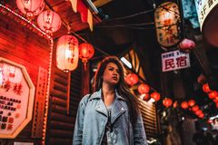 Una mujer presenta en la calle vieja famosa de Jiufen, Taiwán en la noche foto de archivo