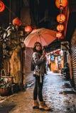 Una mujer presenta en la calle vieja famosa de Jiufen, Taiwán en la noche fotografía de archivo