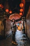 Una mujer presenta en la calle vieja famosa de Jiufen, Taiwán en la noche imagenes de archivo