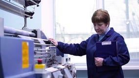 Una mujer presiona un botón en el panel de control  almacen de metraje de vídeo