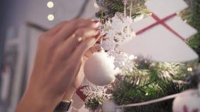 Una mujer prettty joven adorna un árbol de navidad con los juguetes almacen de metraje de vídeo