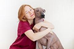 Una mujer que abraza con un perro imagenes de archivo