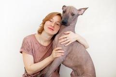 Una mujer que abraza con un perro sin pelo mexicano foto de archivo