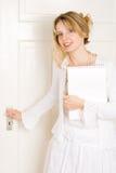 Una mujer que abre una puerta Imagen de archivo