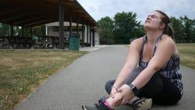 Una mujer que activa experimenta dolor del tobillo durante un funcionamiento en un parque almacen de metraje de vídeo