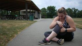 Una mujer que activa experimenta una lesión de rodilla durante un funcionamiento en un parque metrajes
