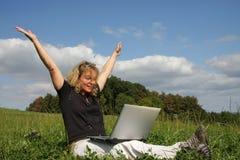 Una mujer que anima con una computadora portátil Fotos de archivo libres de regalías