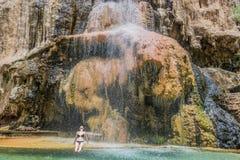 Una mujer que baña la cascada Jordania de las aguas termales del ma'in Imagenes de archivo