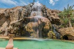 Una mujer que baña la cascada Jordania de las aguas termales del ma'in Fotos de archivo