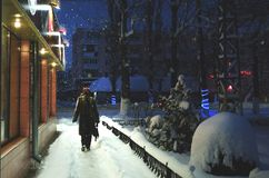Una mujer que camina abajo de la calle en la noche nevosa del invierno Foto de archivo