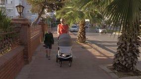 Una mujer que camina con un carro de bebé y un hijo de siete años metrajes