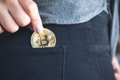 Una mujer que coge y bitcoin de caída en un bolsillo negro de la mezclilla imagen de archivo