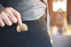 Una mujer que coge y bitcoin de caída en un bolsillo negro de la mezclilla imagenes de archivo