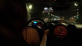 Una mujer que conduce en una carretera en la noche, visión desde el asiento trasero almacen de metraje de vídeo
