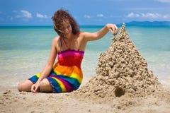 Una mujer que construye un castillo de arena Fotografía de archivo