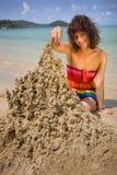 Una mujer que construye un castillo de arena Imagen de archivo libre de regalías