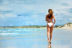 Una mujer que corre a lo largo de la playa en un bikini blanco Imágenes de archivo libres de regalías